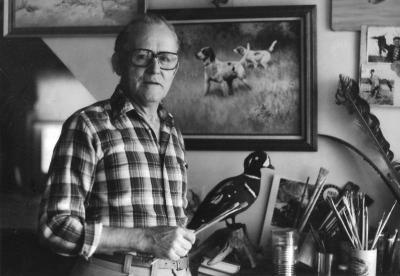 Black and white photo of wildlife artist Bob Hines in art studio.